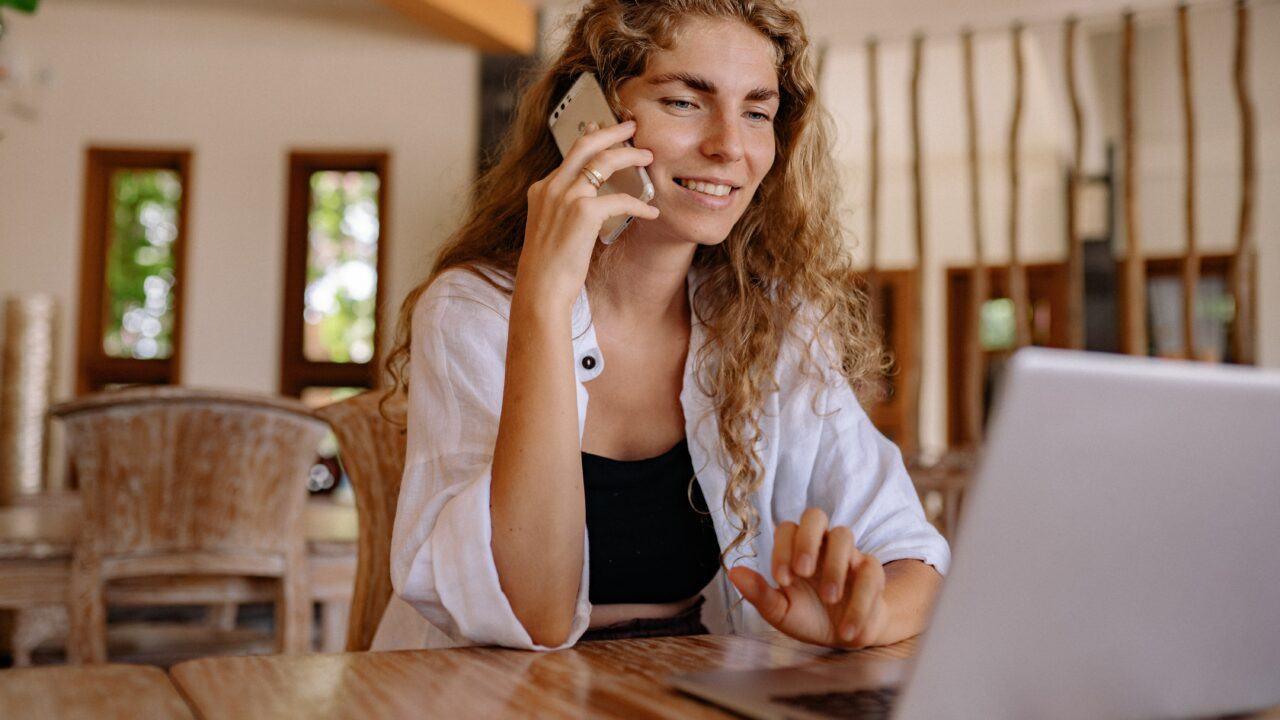 Woman surfing on notebook while having phonecall on mobile